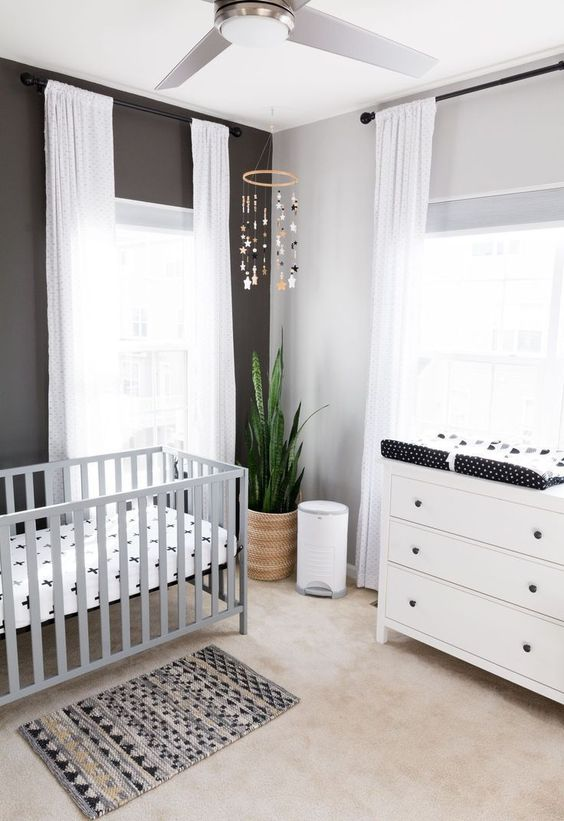 a stylish monochromatic nursery with a white dresser, a grey crib, a black accent wall, a printed rug and bedding, a mobile and white curtains