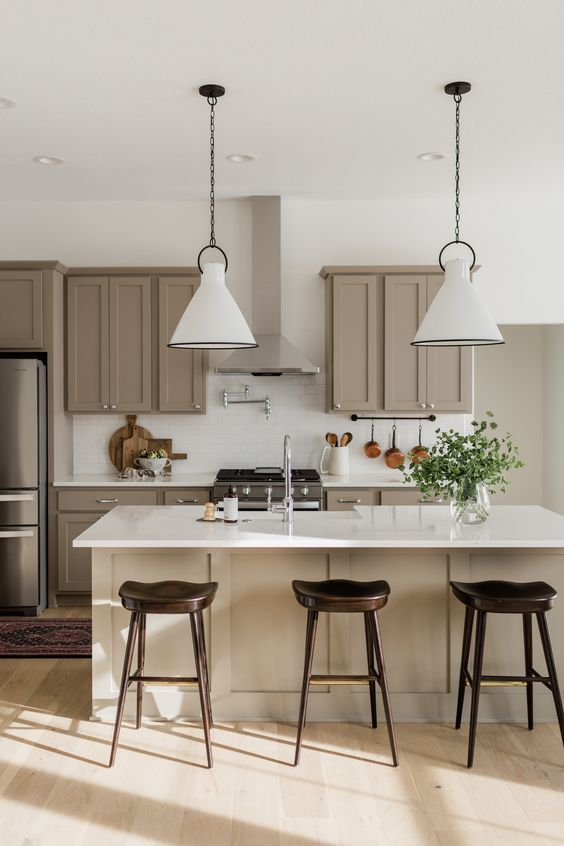 a super stylish modern farmhouse kitchen done in taupe and white, with shaker cabinets, white stone countertops and white subway tiles, white pendant lamps and dark stools