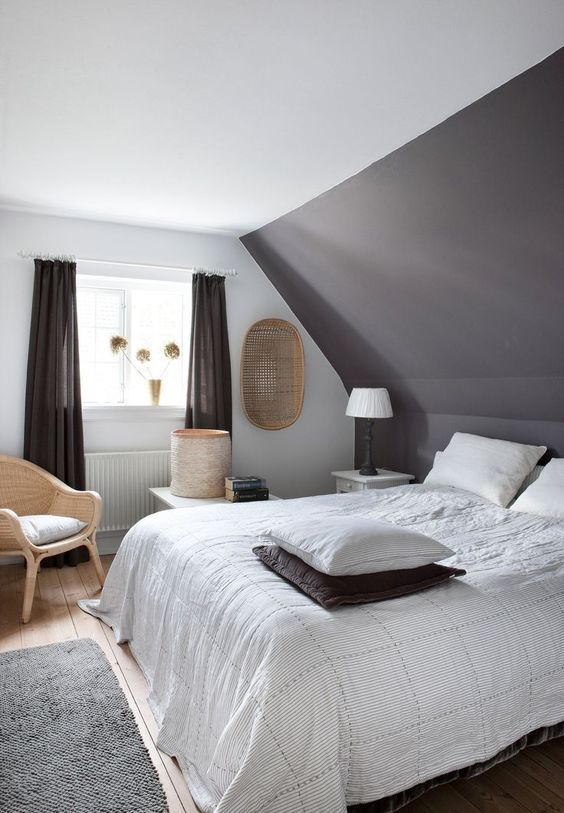 a taupe bedroom with a taupe accent wall, a taupe bed, neutral bedding, black curtains, rattan chair and baskets