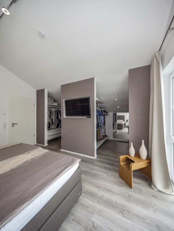 a taupe bedroom with a taupe bed, white and taupe bedding, creay curtains and a walk-in closet integrated right here