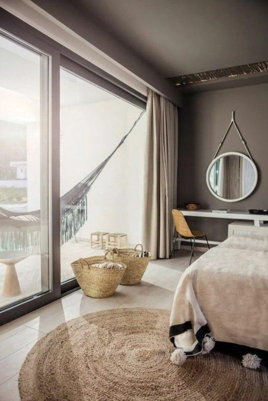 a taupe bedroom with an upholstered bed, a console taht doubles as a vanity, a round mirror and a hammock in the balcony