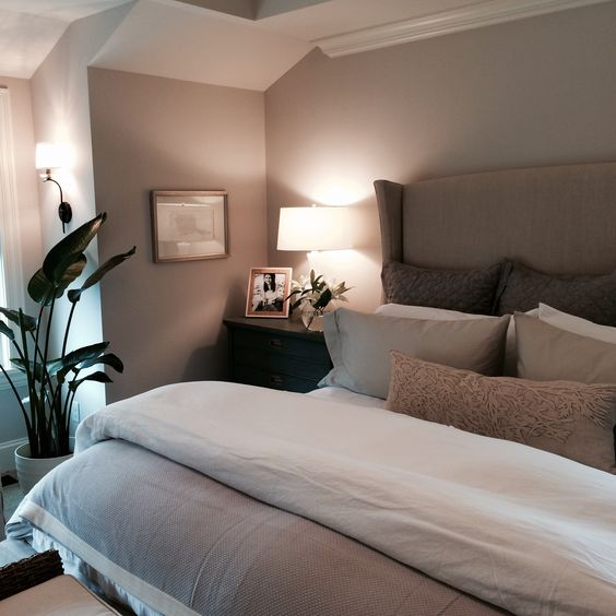 a taupe bedroom with taupe walls, an upholstered bed, dark stained nightstands and lots of lamps plus a statement potted plant