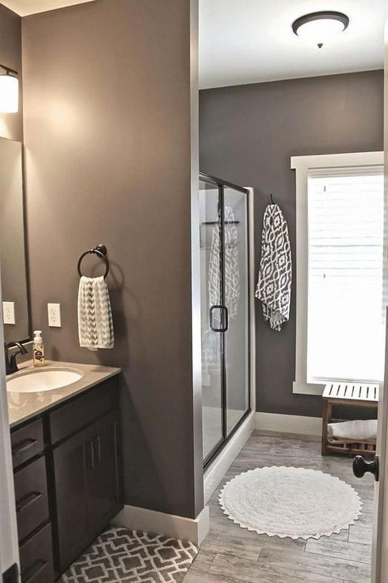 a traditional taupe bathroom with a dark stained vanity, a shower space, a wooden bench, neutral textiles and a large window for natural light