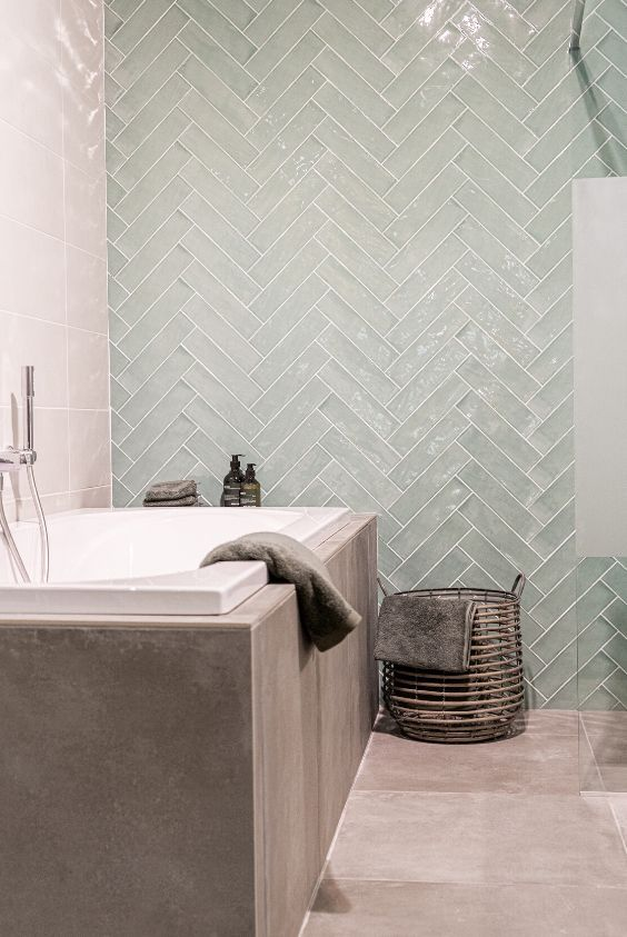 a unique contemporary bathroom clad with taupe tiles and glossy mint chevron ones, with a basket for storage and some neutral textiles