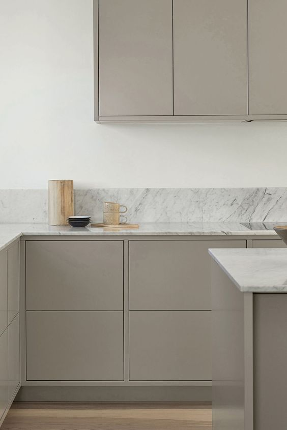 a very minimal kitchen with sleek taupe cabinets, white stone countertops and a backsplash plus gold touches is a stylish solution to rock