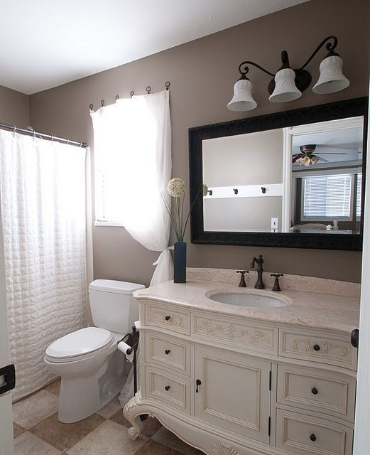 a vintage taupe bathroom with taupe walls, a vintahe ornated vanity, a mirror in a black frame, white appliances and a large sconce