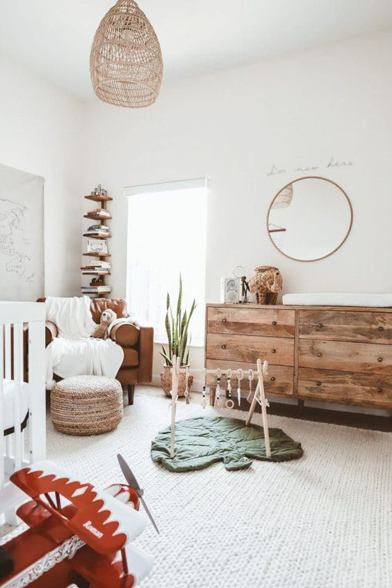a welcoming and airy modern nursery with a white crub, a leather chair, a stained dresser, a woven pouf, a woven lamp and a stained bookshelf in the corner