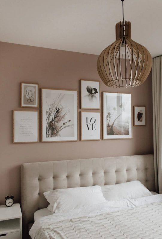 a welcoming bedroom with taupe walls, an upholstered neutral bed, white nightstands, a plywood lamp and a chic gallery wall