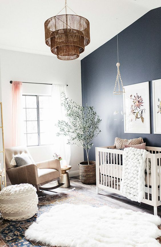 a welcoming boho nursery with a navy accent wall, a white crib and a tan rocker chair, layered rugs, a pendant lamp and some knit pieces