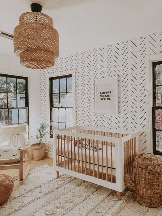 a welcoming boho nursery with a printed wall, white and stained furniture, a cactus basket for storage, neutral textiles and a woven pendant lamp