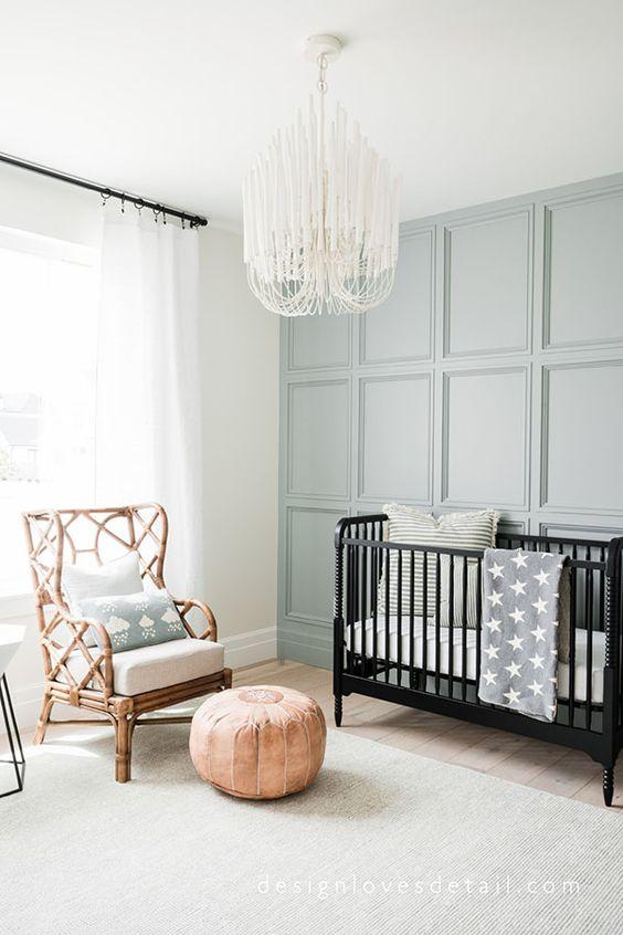a neutral nursery with a styish panelled wall