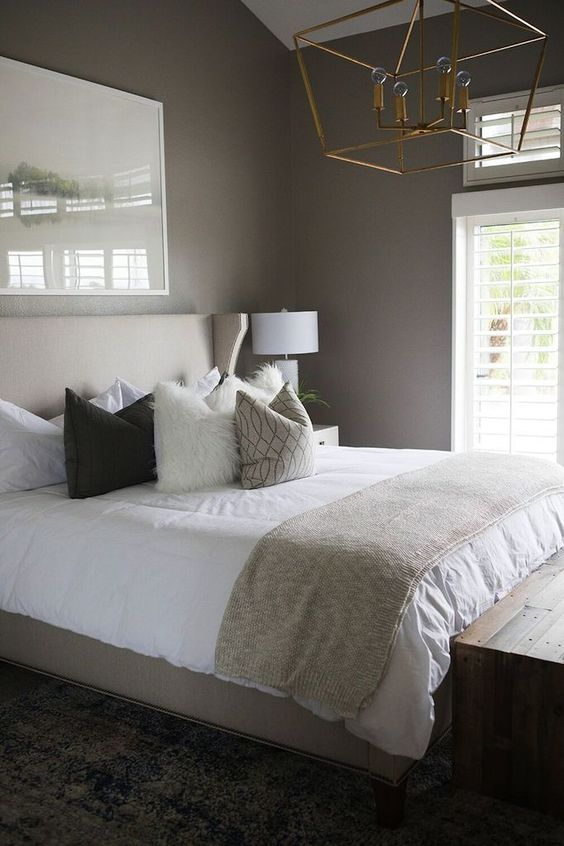 a welcoming taupe bedroom with a tan bed, neutral and printed bedding, a gilded chandelier and a wooden bench