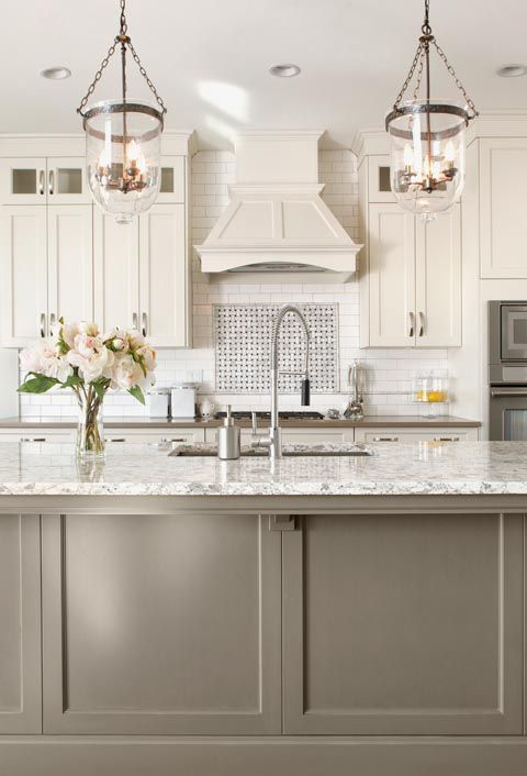 a white vintage kitchen with shaker cabinets, a white tile backsplash and white countertops, a taupe kitchen island with a white countertop