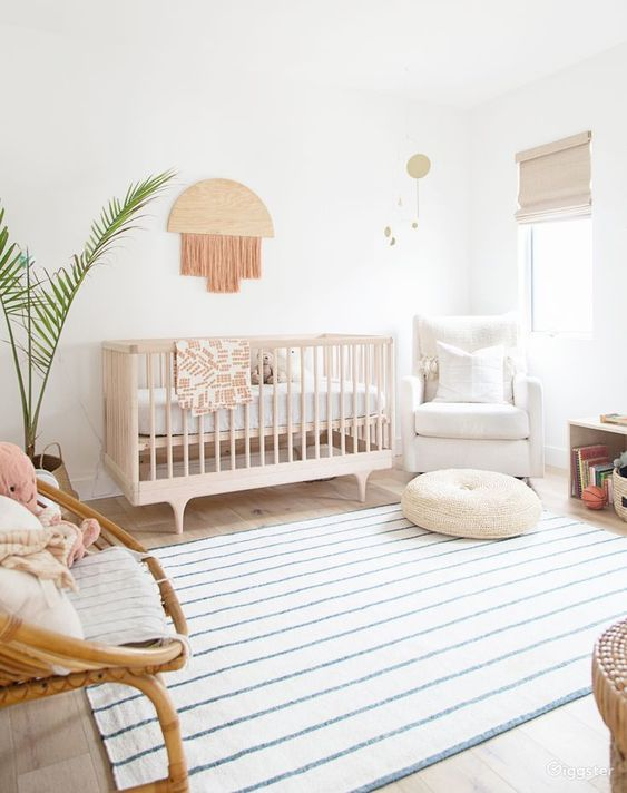 an airy boho nursery with a stained crib, a rattan and upohlstered chair, a fringe decoration, a printed rug plus a potted plant is a cool idea