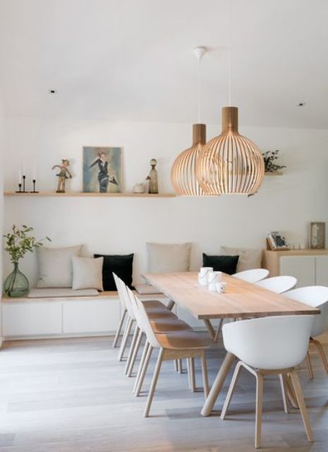 an airy contemporary dining room with a built-in storage bench, pillows, a light-stained table and white chairs, pendant plywood lamps