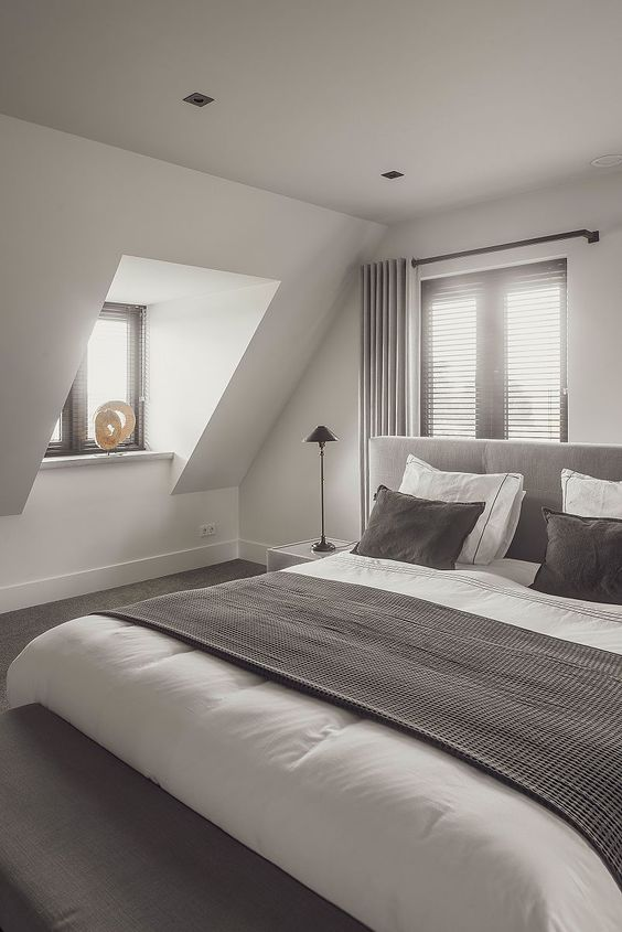 an elegant attic bedroom with windows with dark shades, a grey bed with taupe and white bedding, table lamps