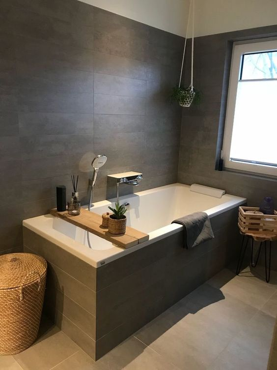 an elegant bathroom clad with taupe tiles, a bathtub clad with them, some potted greenery, baskets and crates for storage