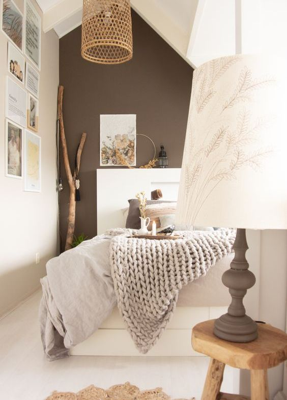 an eye-catchy boho bedroom with a taupe accent wall, a gallery wall, a white bed and neutral bedding, an artwork and a woven lamp