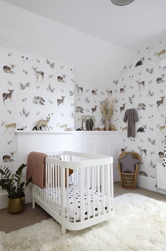 an eye-catchy contemporary nursery with flora and fauna wallpaper, a white crib and paneling, a little peacock chair and a fluffy rug