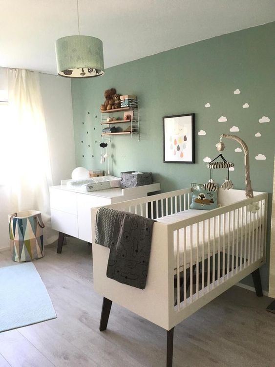 an inviting nursery with a green accent wall, white and black furniture, an open shelf, a green pendant lamp and some art is amazing