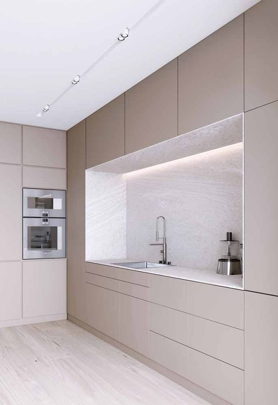 an ultra-minimalist sleek taupe kitchen with a white stone backsplash and countertops and built-in appliances plus built-in lights