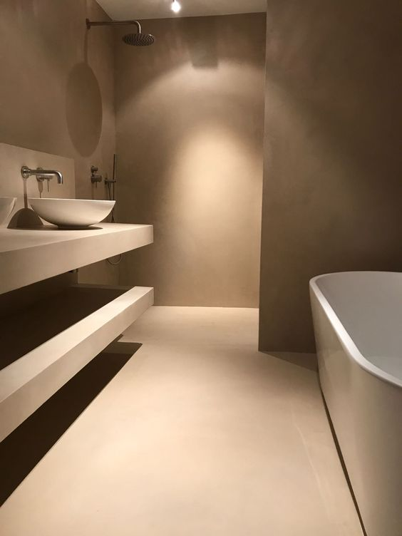 an ultra-minimalist taupe bathroom with matte walls and a floor, open shelves, an oval taupe tub and a white bowl sink is amazing
