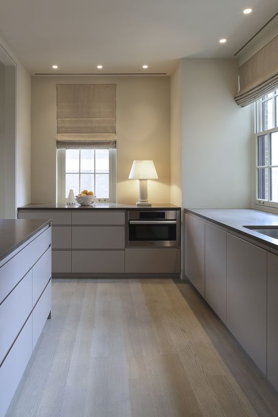 an ultra-minimalist taupe kitchen with sleek cabinets, black stone countertops, woven shades and small windows looks very laconic