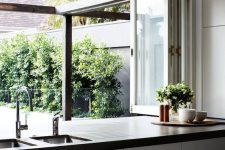 03 a folding window opens the kitchen to outdoors, and turns it into an outdoor-indoor space easily and with style