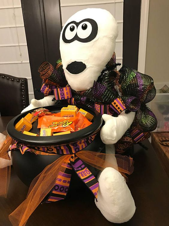 a mummy holding a witch's cauldron with sweets and candies is a great idea for styling your porch at Halloween