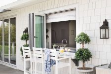 07 a lovely coastal outdoor dining space wiht a pass through window, tall white stools and a floating table, which is a windowsill