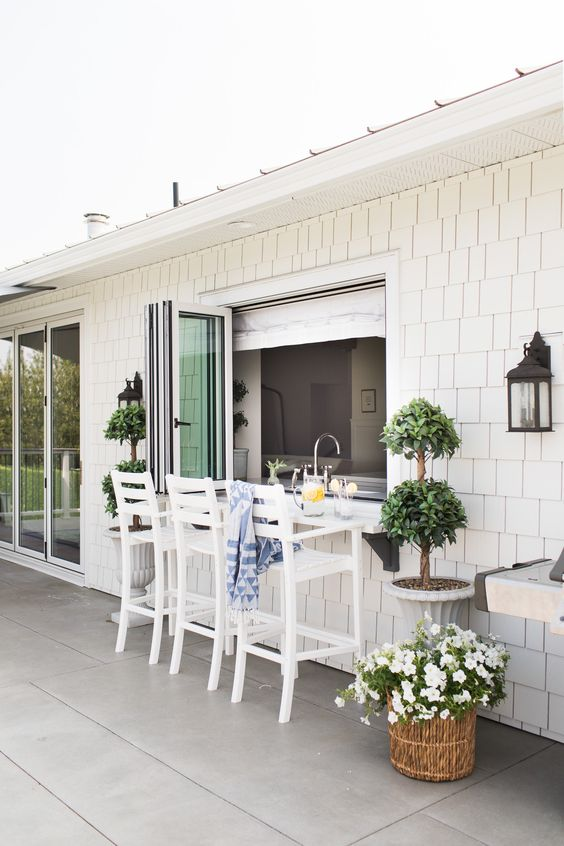 a lovely coastal outdoor dining space wiht a pass through window, tall white stools and a floating table, which is a windowsill