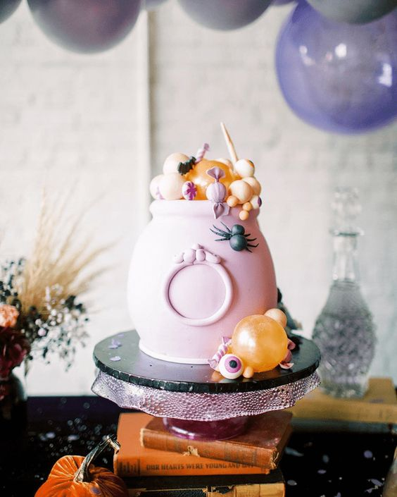 a pink cauldron with candies and sweets in pastel colors is a great way to serve some food in a truly Halloween way