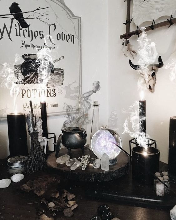 a chic witch's nook with a cauldron with smoke, candles, crystals, a sphere and some signs is a gorgeous idea for Halloween