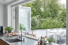 08 a modern kitchen with light-stained cabientry, dark countertops, a white folding window to outdoors that makes bringing food to the outdoor dining space easier
