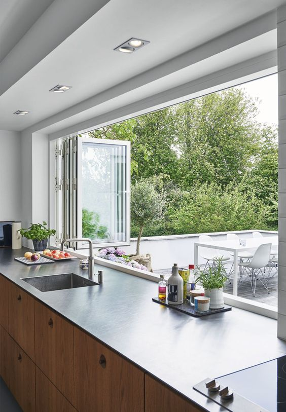 a modern kitchen with light stained cabientry, dark countertops, a white folding window to outdoors that makes bringing food to the outdoor dining space easier