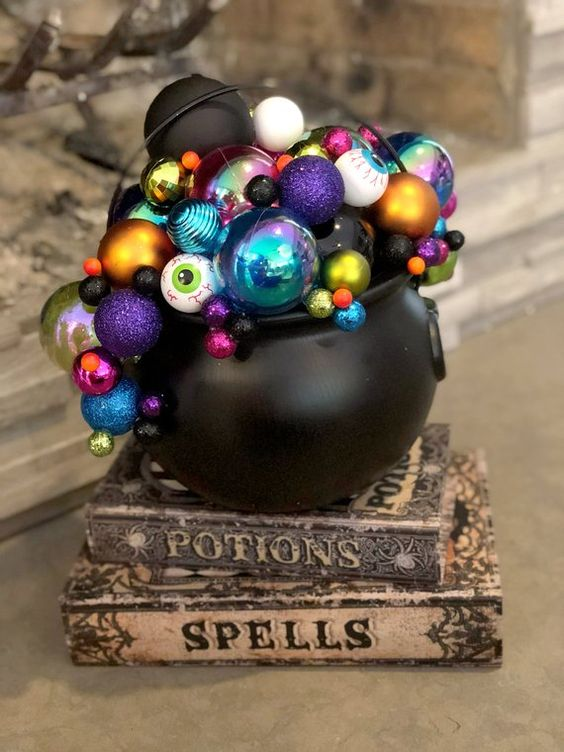 a couple of spellbooks with a cauldron on top and colorful eyeballs and ornaments for a lovely and whimsy Halloween decoration