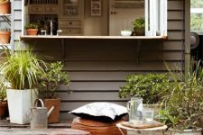 09 a cozy boho space with a folding window, leather poufs and potted greenery is amazing to have drinks here