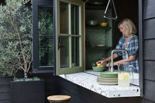 11 a black outdoor space with tall stools, a folding pass through window, a terrazzo windowsill that doubles as a table