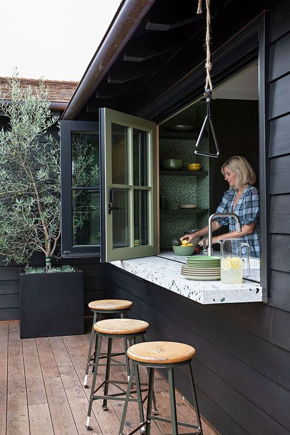 a black outdoor space with tall stools, a folding pass through window, a terrazzo windowsill that doubles as a table