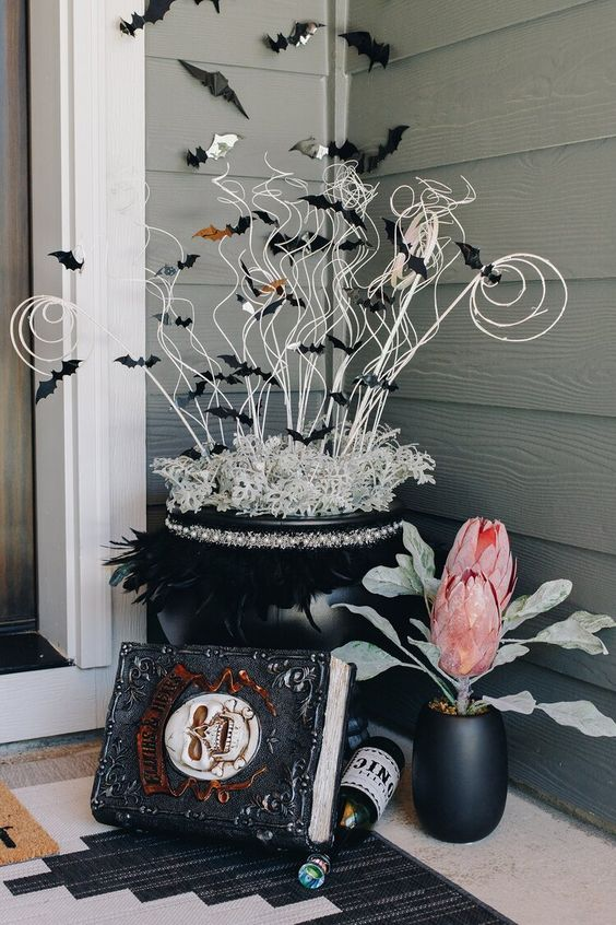 crazy Halloween front porch decor with a spellbook, a black planter with oversized blooms, a black cauldron with twigs and black bats