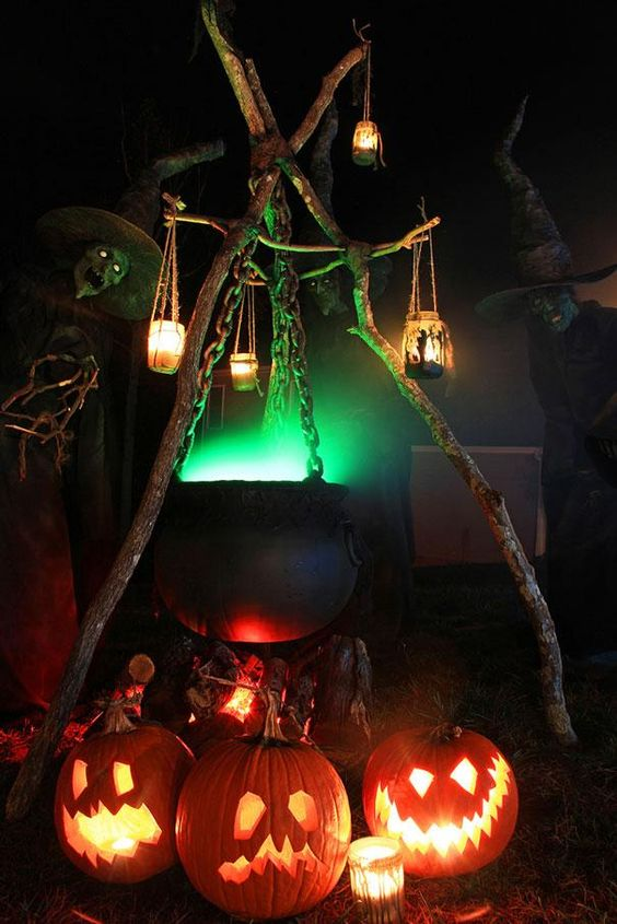 a fab Halloween outdoor decoration of a cauldron with green smoke, candle lanterns, jack-o-lanterns under it is a lovely idea