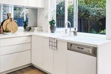 12 a minimalist white kitchen with sleek cabinets, a window backsplash and a folding window for fresh air or as a pass through window