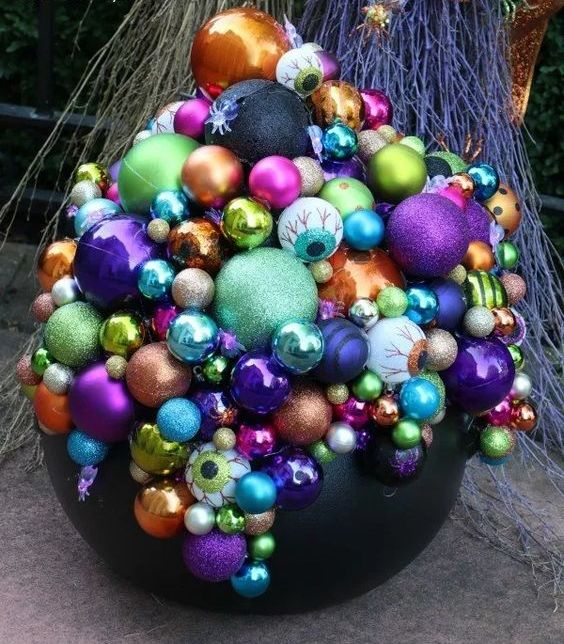 a Halloween decoration of a black cauldron and lots of colorful Christmas ornaments and eyeballs is bold and lovely