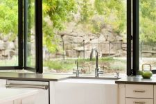 13 a neutral farmhouse kitchen with dark countertops, a black folding window and cool and fresh views is amazing