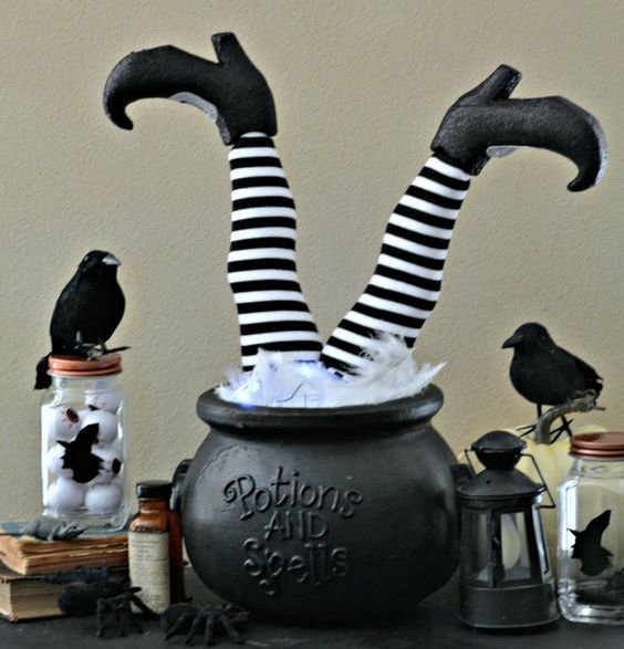 a Halloween decoration of a cauldron with witch's legs, candle lanterns, blackbirds and vintage books is amazing