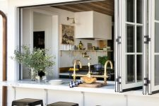 14 a pretty farmhouse space with a large French folding window, a floating table and black stools is a lovely solution