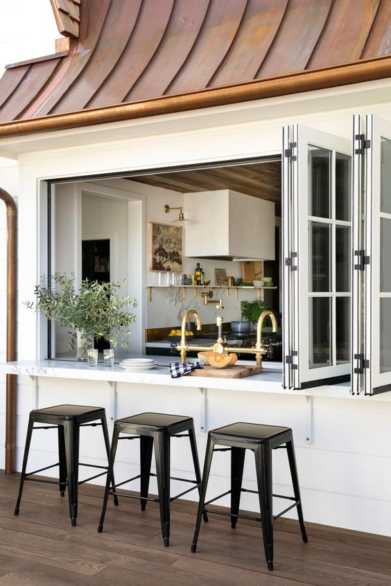 a pretty farmhouse space with a large French folding window, a floating table and black stools is a lovely solution