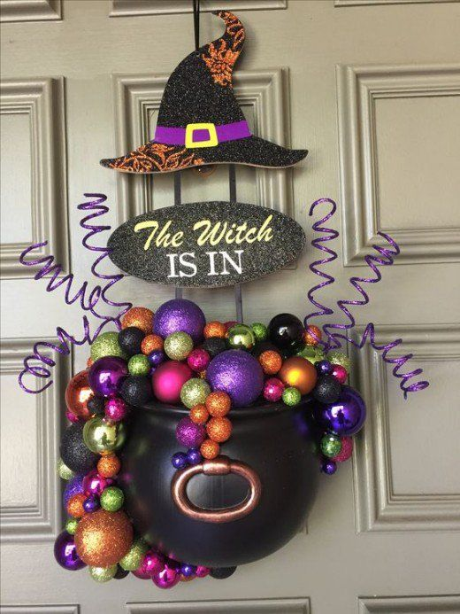 a Halloween door decoration of a witches' cauldron with colorful glitter Christmas ornaments, a witch hat and some curls is a cool idea