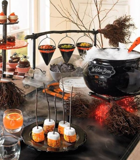 a Halloween party sweets table with a cauldron with lights, sweets, popcorn, marshmallows and macarons is amazing