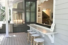 16 a neutral farmhouse space with a folding pass through window, a floating dining table and rattan stools is a lovely idea to go for